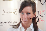 Woman studies a chemistry equation poster