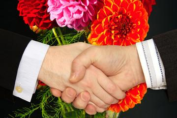 Businessmen shaking hands on the Flower Background