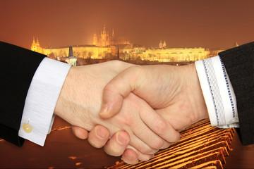 Businessmen shaking hands in front of Prague Castle