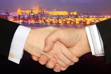 Businessmen shaking hands in front of Prague in night