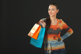 Young elegant female in sweater holding purchases