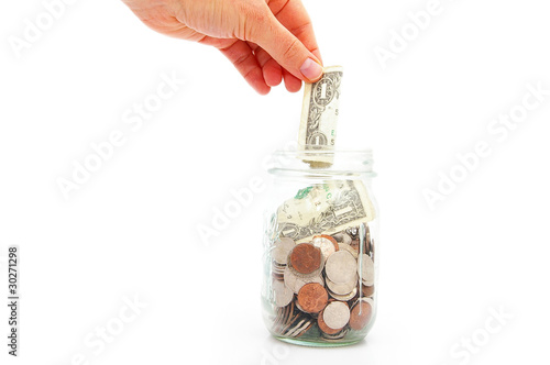 hand putting a dollar in a coin jar