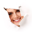 cheerful teen girl peeping surprised through hole in white paper