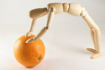 Woodman pushing an orange