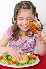 Mädchen isst Hähnchen