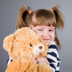girl sits  with a toy bear