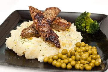 Slices of beef mashed potato, peas and broccoli