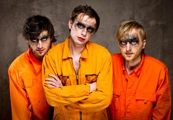 Three guys in orange uniforms indoors