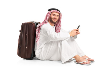 Arab man sitting near a suitcase and typing a text message on hi