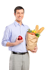 Smiling man holding an apple,a bag full with bread and vegetable