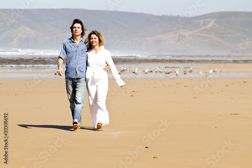 Young couple in love walking at the beach