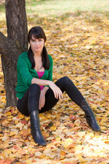 beautiful girl with dark hair resting in autumn park