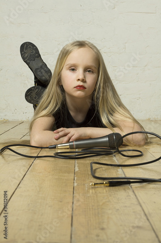 Little girl singer in black lies with the microphone