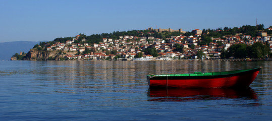Old town on the lake with red boat
