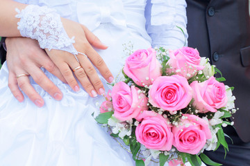 Hands with wedding rings about a wedding bouquet.
