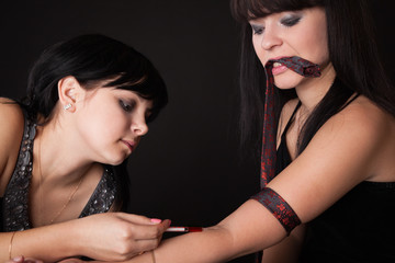 a girl is stabing to her girlfriend a drug