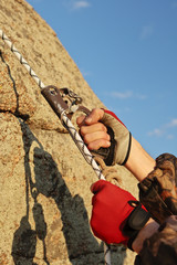 Hands of climber I work with equipment on rock.