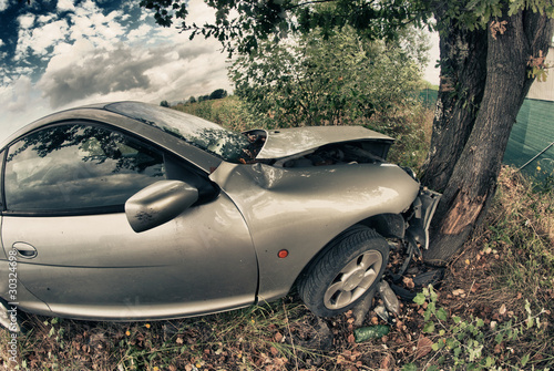 Broken Car After an Accident against a Tree