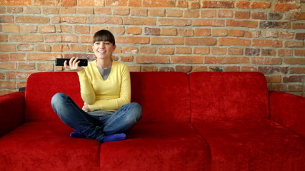 Woman on a sofa with a tv remote control
