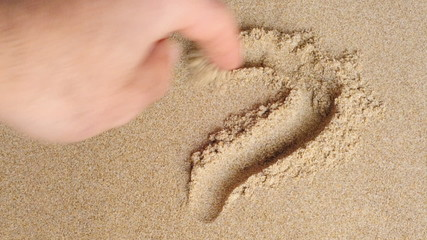someone drawing a heart in the sand