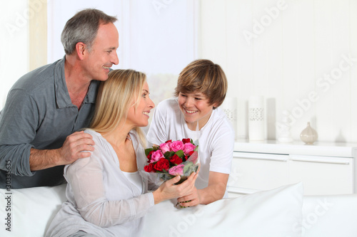 Son offering bunch flowers on mother's birthday