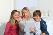 Family having fun at home using electronic tablet