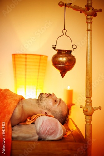 Man having a shirodhara massage in a salon