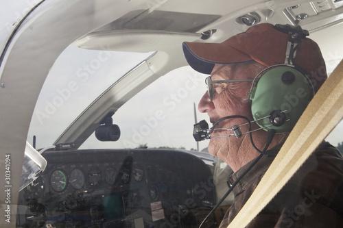Leinwanddruck Bild Senior Pilot in the cockpit of a Cessna twin engine