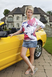 Wealthy young woman standing beside car poster