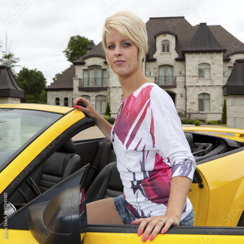 Wealthy young woman getting into a convertible car