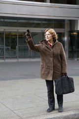 Outdoor business woman hailing a taxi cab