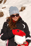 Girl with red gloves and a big snowball