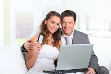 Bride and groom doing shopping on inernet at home