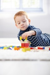 Lovely 3 year old playing with cubes at home