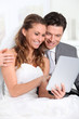 Bride and groom using electronic tablet