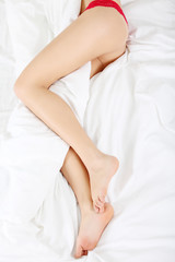 Woman legs on bed