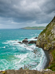 Cliffs under thunder clouds and turquoise ocean