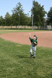Boy in baseball uniform playing catch
