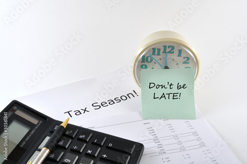 Tax Season. Don`t be late. Concept Image with calculator and clo