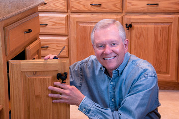 Senior male doing home repair - cabinet knob replacement