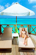 Young woman tans on a terrace of water villa on ocean Maldives..