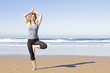 Young healthy woman doing yoga exercises at the beach