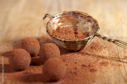 chocolate truffles cocoa powder dusted and sieve, shallow dof