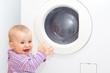 Lachendes Kleinkind freut sich an der Waschmaschine