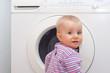 Kleines Mädchen interessiert sich für die Waschmaschine