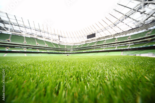 Fotobehang Stadion green-cut grass in large stadium at summer day