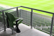 One green plastic fold-flat seat on tribune of large stadium