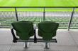 Two green plastic seats on tribune of large stadium