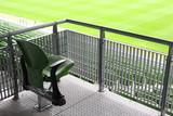 One green plastic fold-flat seat on tribune of large stadium