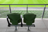 Two green plastic seats on tribune of large stadium